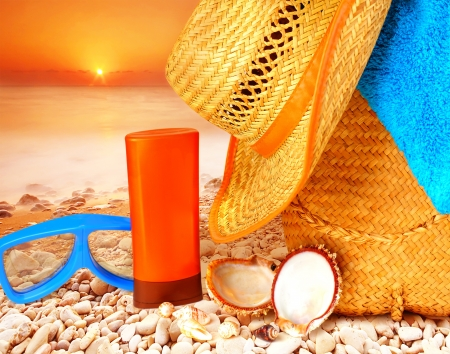 Closeup beach items on sunset on the stony seashore, hygiene accessories, snorkeling mask, sunscreen, hat, bag and towel, summer activities photo