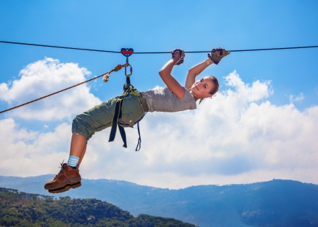 Active happy woman overhanging on tightrope in the mountains on blue sky background, climbing sport, mountaineering adventure, summer trekking concept photo
