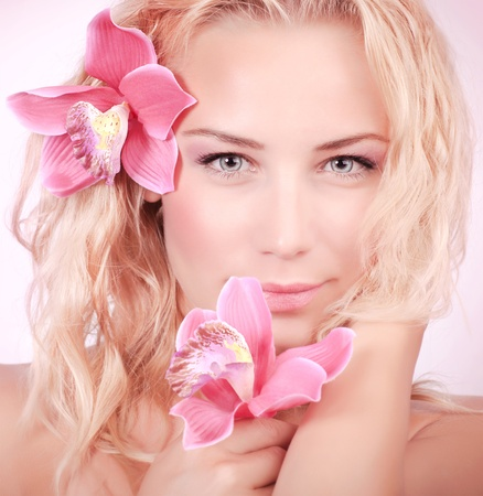 Closeup portrait of attractive blond female with gentle pink orchid flower in hair, skin care, perfect natural makeup, beauty salon  photo