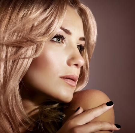ragazze bionde: Closeup ritratto di donna alla moda giovane donna con lucida i capelli biondi isolato su sfondo marrone, salone di bellezza di lusso