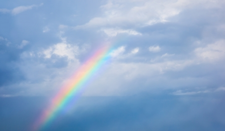 outdoor photo: Beautiful colorful rainbow in cloudy sky, abstract background, natural phenomenon, bright multicolors sun beam after rain, meteorology concept