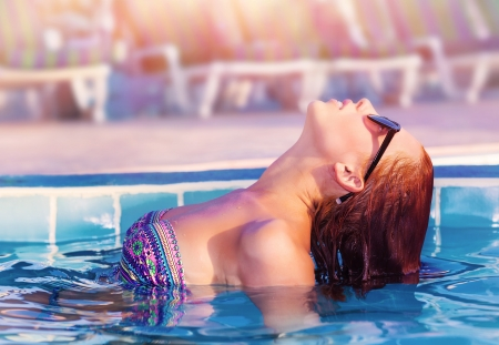Side view of cute woman posing in the pool, swimming in poolside, having fun in luxury tropical resort, sunny day, enjoying day spa, summer vacation concept
