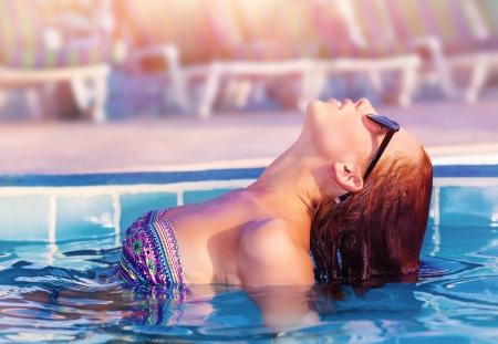 Vista lateral de la mujer linda posando en la piscina, nadar en la piscina, que se divierten en el centro turístico tropical de lujo, día soleado, en el balneario día, el concepto de vacaciones de verano