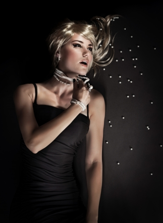 woman black background: Attractive seductive woman tearing her pearl beads isolated on black background, broken luxury jewellery, desire concept