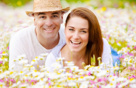 Closeup portrait of happy couple lying down on fresh daisy field, romantic date, summer vacation, love concept photo