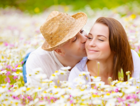 Two happy lovers laying down on white floral meadow, handsome guy kissing his cute girlfriend, relaxation outdoor, romance concept photo