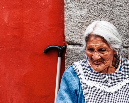 MEXICO CITY, MEXICO - JULY 14  portrait of unidentified old Mexican lady, sits next to traditionally colorfully painted house walls on July 14, 2012 on main street market in Mexico City, Mexico