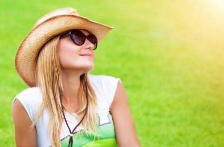 field glass: Cute female sitting down on green field in sunny day, wearing straw hat and stylish sunglasses, enjoying nature, summer time concept Stock Photo