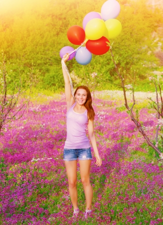 Happy young woman holding in hands many colorful balloons, having fun on purple floral field, summer time season, freedom concept Stock Photo - 20054107