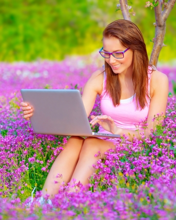 field study: Cute woman sitting down in beautiful floral garden with laptop, wearing glasses, working outdoors, studying on university backyard, business and success concept