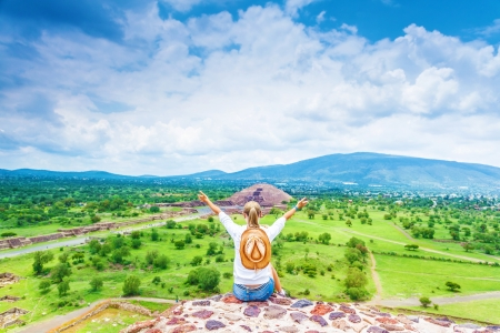 pyramid peak: Back side of woman sitting with raised up hands on the top of mountains and enjoying view of Mexican Teotihuacan pyramid, travel and tourism concept Stock Photo