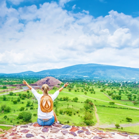 top down: Traveler girl sitting down on the top of mountains with raised up hands, rear view, Teotihuacan pyramid in Mexico, exciting adventure, hiking tourism concept