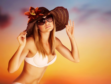 Seductive female on the beach, luxury model wearing stylish sunglasses and hat posing on beautiful orange sunset background, hot summer vacation concept