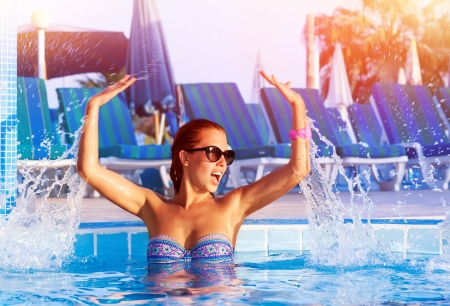 Happy pretty girl having fun in the pool, cute playful female splashing water in swimming pool, relaxation and play in poolside, summer vacation concept Stock Photo - 20054109