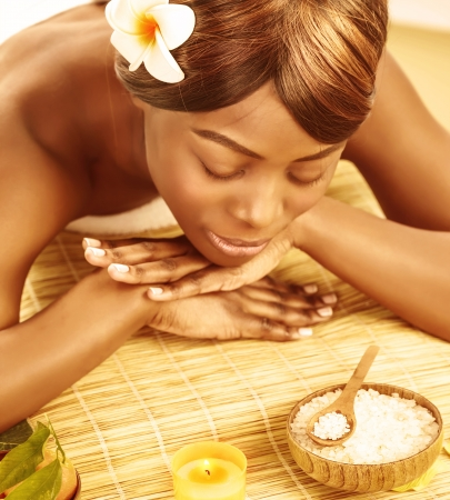 Beautiful african woman with closed eyes and frangipani flower lying down on massage table photo