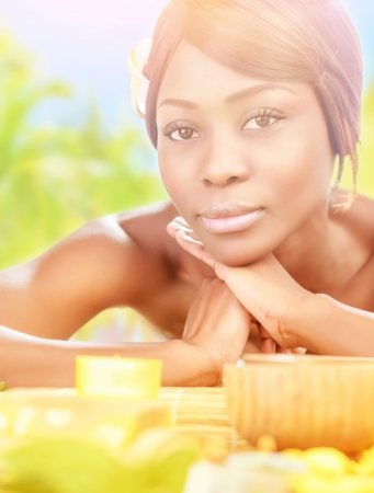 Closeup portrait of pretty african female lying down on massage table on the beach photo