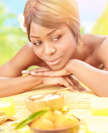 Attractive black woman relaxed on luxury spa resort, lying down on massage table with frangipani flower in hair on the beach in sunny day, healthcare concept  photo