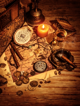 booty pirate: Ancient treasures border, pirates booty still life on wooden table, compass and map, golden coins and aged medallion, adventure and picaroon concept