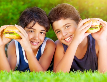Closeup portrait of two happy boys eating big tasty fatty burgers outdoors, lying down on green field and enjoying sandwich with cheese, meat and vegetables photo
