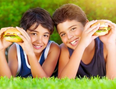 HAMBURGESA: Retrato de dos ni�os felices comiendo grandes sabrosas hamburguesas grasos al aire libre, acostado en campo verde y disfrutar de s�ndwich con queso, carne y verduras