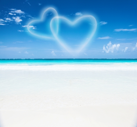 Romantic seaside resort, beautiful seascape, two heart shaped clouds in the blue sky, honeymoon vacation, paradise beach, summer holiday concept photo