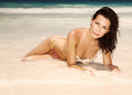 Gorgeous female lying down on the beach, sexy slim model posing on sandy coastline photo