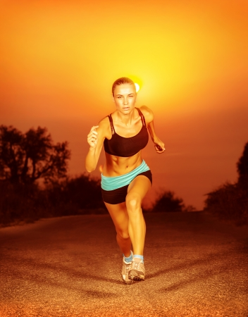 Beautiful sporty woman run on the road at sunset photo