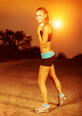 Happy sporty woman doing exercise at sunset photo