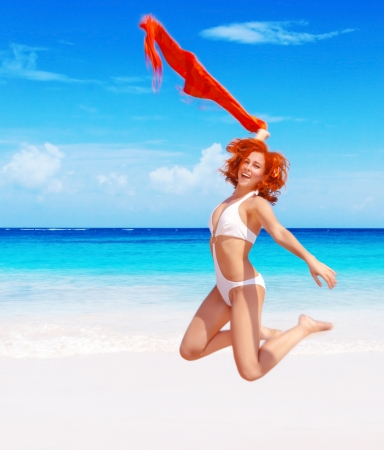 scarf beach: Happy smiling woman jumping on the beach with red shawl
