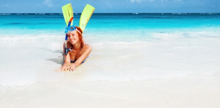 Happy diver girl lying down on beautiful sandy beach photo