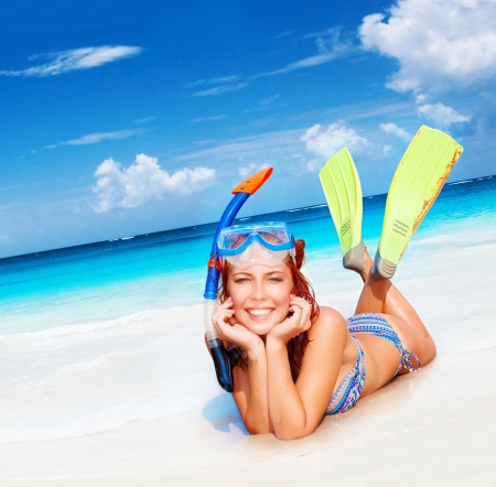 flippers: Happy diver woman lying down on beautiful sandy beach Stock Photo