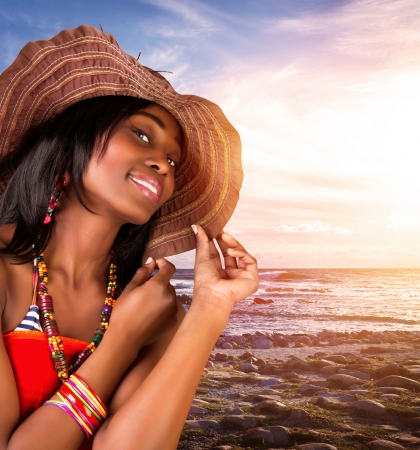 Closeup portrait of beautiful african woman on the beach, sexy model posing on seashore on sunset, wearing stylish hat and fashionable accessories, summer vacation photo