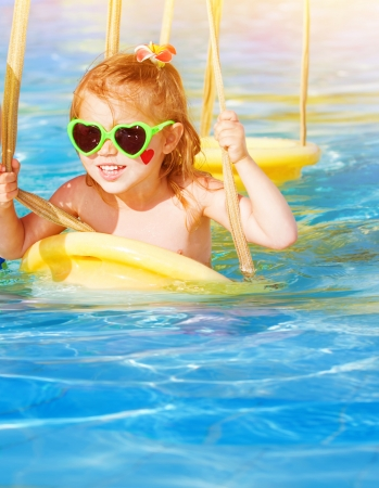 Closeup portrait of cute baby girl swinging on water attractions in aquapark, wearing sunglasses, red heart on cheek, enjoying summer holidays, happy childhood concept photo