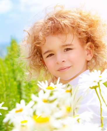 Closeup portrait of cute baby boy with beautiful curly hair on daisy field in sunny day, summer time concept photo