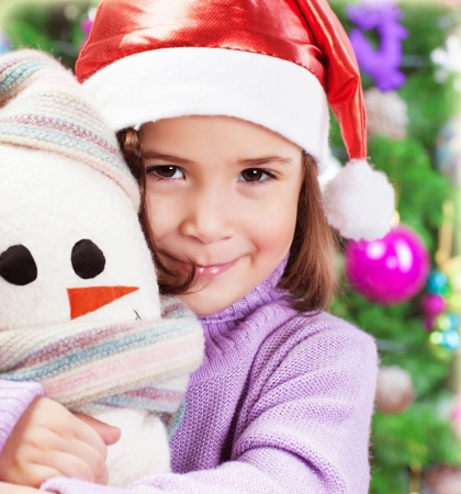 Closeup portrait of cute little girl holding snowman soft toy over Christmas tree background, wearing red Santa hat Stock Photo - 20442868