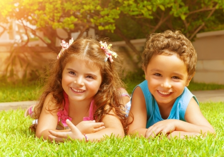 Two happy kids lying down on green grass, brother and sister enjoying warm sun light, beat friends, summer holiday photo