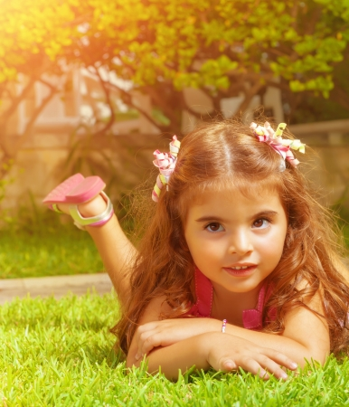 Closeup portrait of cute arabic baby girl lying down on green grass field on backyard, carefree lifestyle, happy childhood concept photo