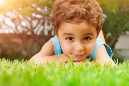 Closeup portrait of cute arabic little boy lying down on green grass field, resting outdoors on backyard, summer holidays concept photo