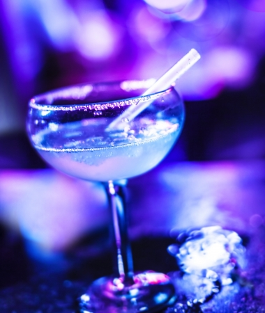 night club interior: Frozen Margarita cocktail, alcoholic beverage in the bar, sweet tasty booze in neon light in the pub, holiday celebration, luxury night life Stock Photo
