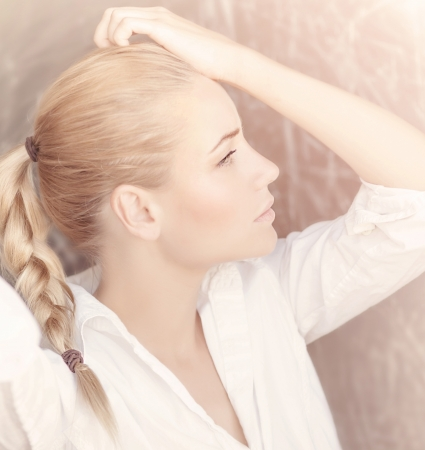 Closeup portrait of seductive woman isolated on tender pink background, profile of cute blond girl with pigtail hairstyle, beauty concept photo