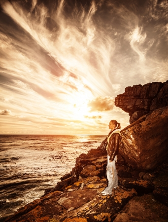 Traveler girl on the cliff, beautiful sunset on seascape, photographer woman, active lifestyle, expedition to mountains, travel concept photo