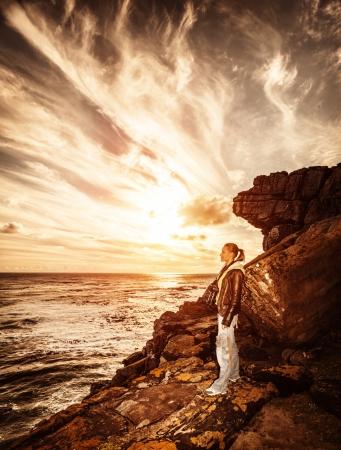 Ragazza viaggiatore sulla scogliera, bel tramonto sul paesaggio marino, fotografo donna, stile di vita attivo, spedizione alle montagne, concetto di viaggio