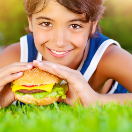 Closeup on cute boy lying down on green grass and eat delicious hamburger, having lunch outdoors, enjoying picnic, healthy food concept photo