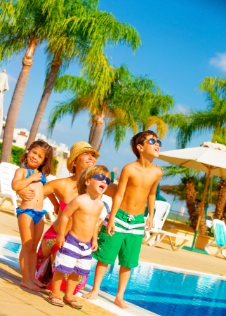 乳幼児: かわいい大家族空のプールサイドや外観の近く立って、夏の休日、顔の表情、ビーチ、愛と友情をコンセプトにリラクゼーションを楽しむ