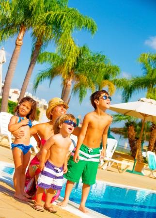 Leuke grote familie die zich in de buurt van het zwembad en kijk omhoog in de lucht, genieten van de zomer vakantie, gelaatsuitdrukking, ontspanning op het strand, liefde en vriendschap begrip