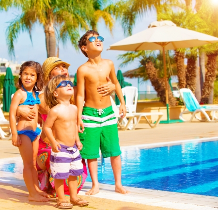 pool fun: Cute happy family having fun near pool on luxury tropical resort, mother with children looking up in sky, summer holidays, love concept Stock Photo