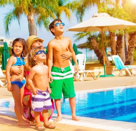 Leuk gelukkig gezin plezier de buurt van zwembad op luxe tropische resort, moeder met kinderen op zoek in de hemel, zomervakantie, liefde concept