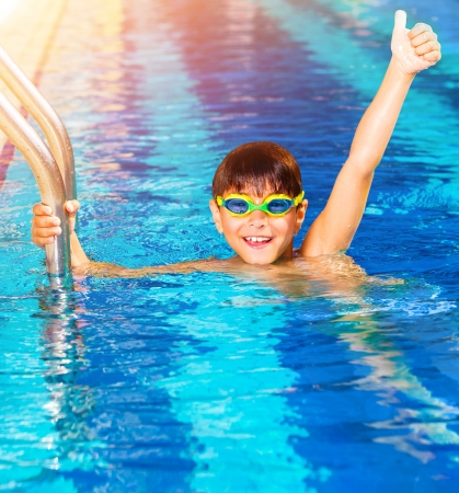 Closeup on little boy wearing swimming goggles in the pool, junior swimming competition, happy winner with raised up hand, summer time sport Stockfoto