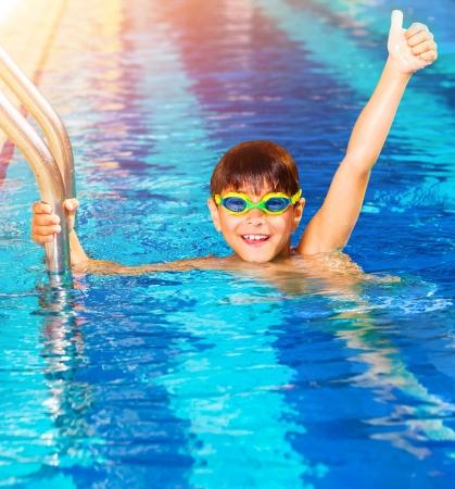 niños felices: Primer plano de niño pequeño que lleva gafas de natación en la piscina, competencia de natación juvenil, feliz ganador con la mano levantada, deporte verano Foto de archivo