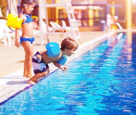 boy jumping: Ni�o lindo saltando en la piscina, hermano y hermana que se divierten en la piscina, atracciones de agua, lujoso complejo de playa, vacaciones de verano, la infancia feliz